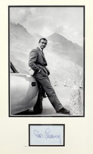 A photograph of Sean Connery as 007 with the Goldfinger Aston Martin DB5 in the Furka Pass, mounted with an autograph